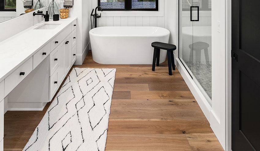 Bathroom with freestanding tub white vanity sink runner rug is