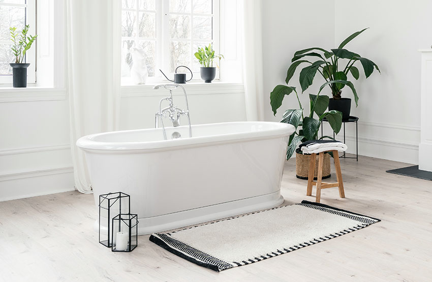 Light bathroom with Scandinavian interior design with tub and rug ss