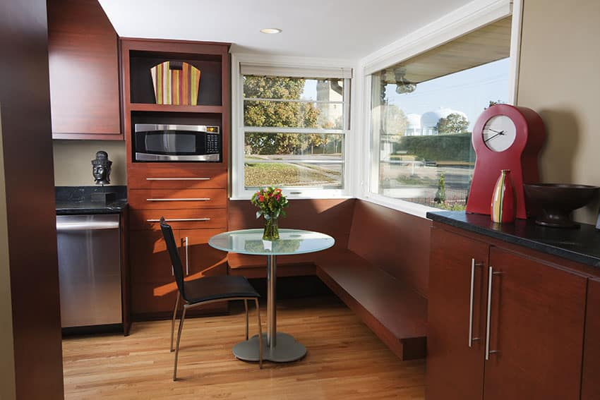 Breakfast nook with reddish brown cabinet glass windows