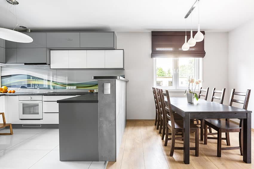 Kitchen and dining with gray cabinets glossy backsplash black countertop pendant lights rollup curtain