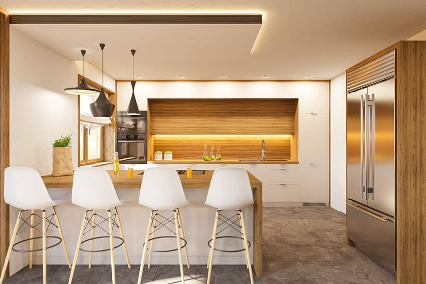 Kitchen with counter bar stools cove lighting pendant lights wooden caged stainless refrigerator
