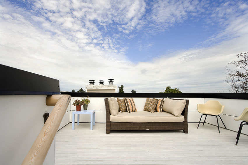 Rooftop with silicone roof coating and rattan sofa