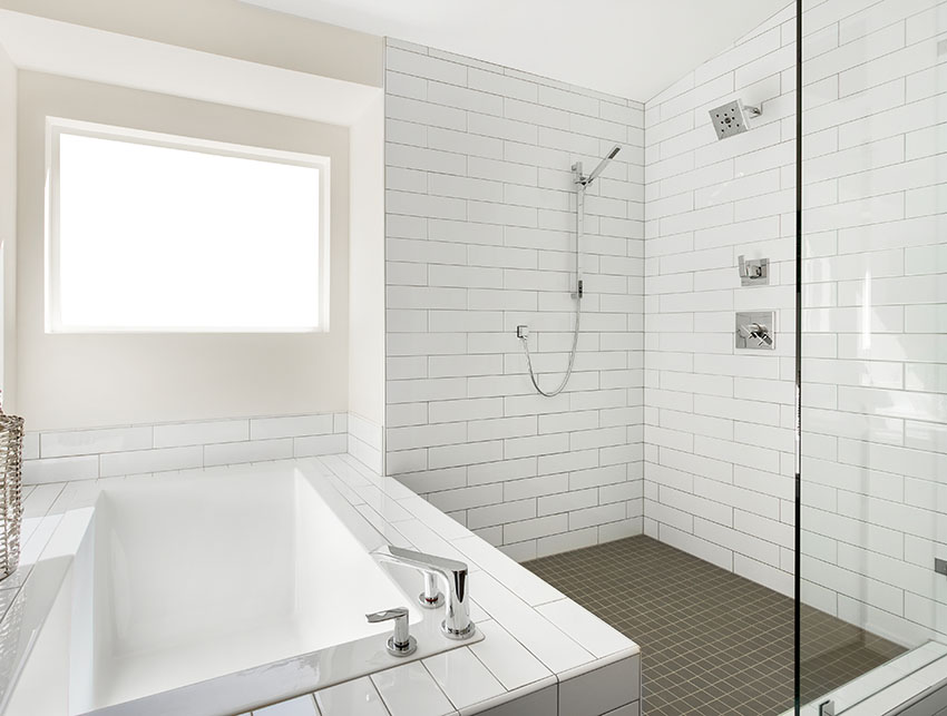 Shower area with tub and stainless spread fit faucet white tiles is