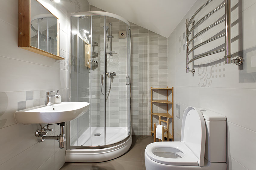 Small bathroom with glass shower door wall mounted sink
