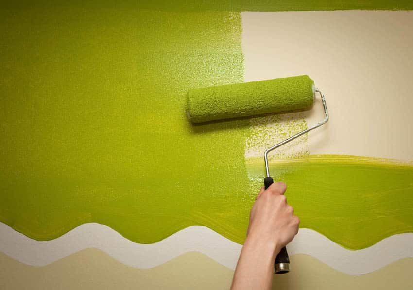 Applying green paint on a wall with paint roller