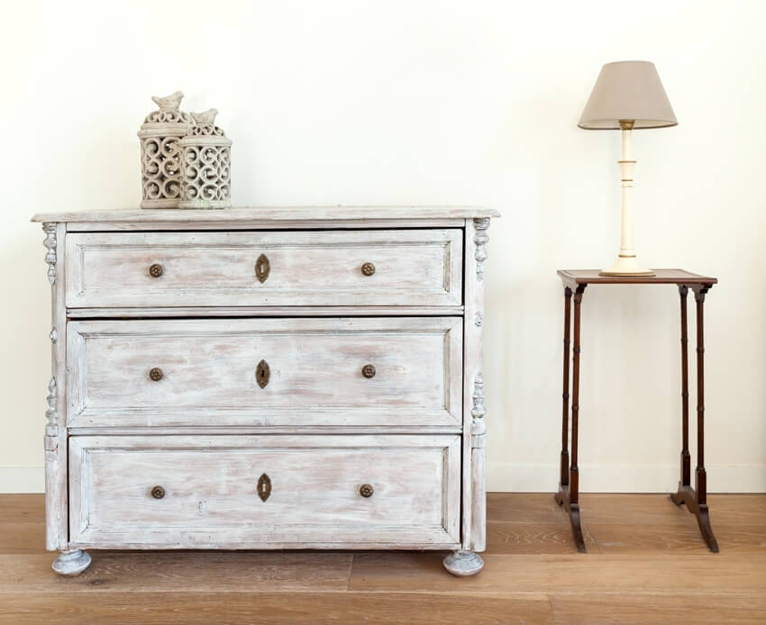 Bachelor's chest dresser and table with lamp in retro style interior