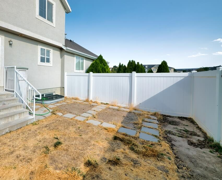 Backyard of a two storey gray house with white vinyl fence