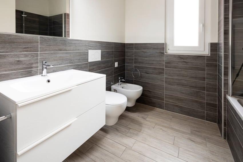 A bathroom with elegant minimalist halfway brown tile walls