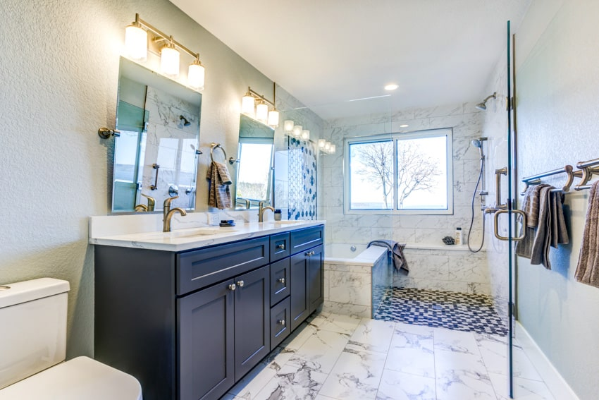 Bathroom with gray and white elements countertop wood cabinet mirror shower area