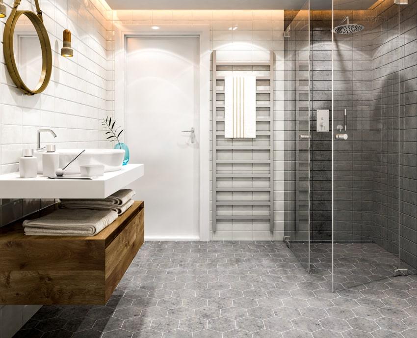 Bathroom with gray hexagonal tiles glass shower door round mirror sink wood drawer