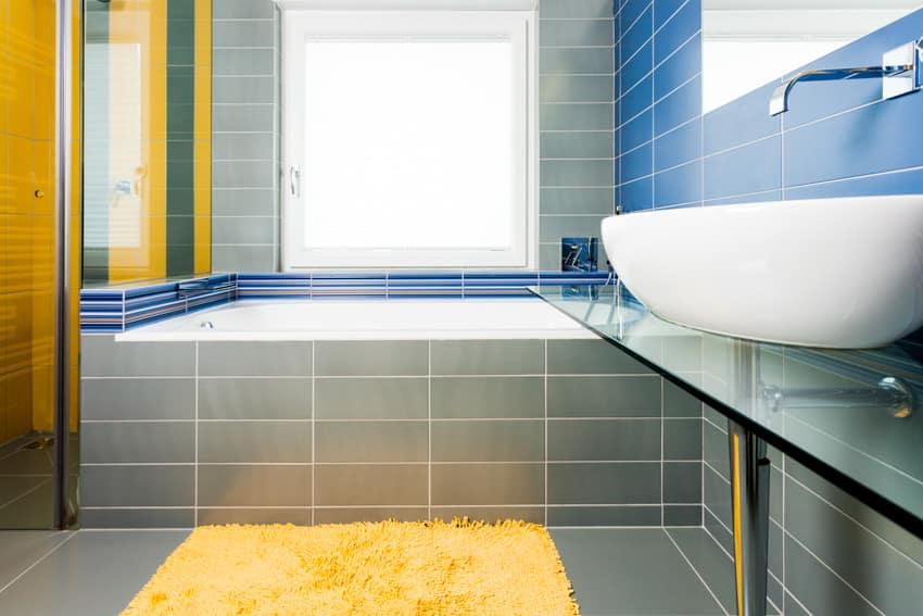 Bathroom with gray tiles basin sink glass divider rug