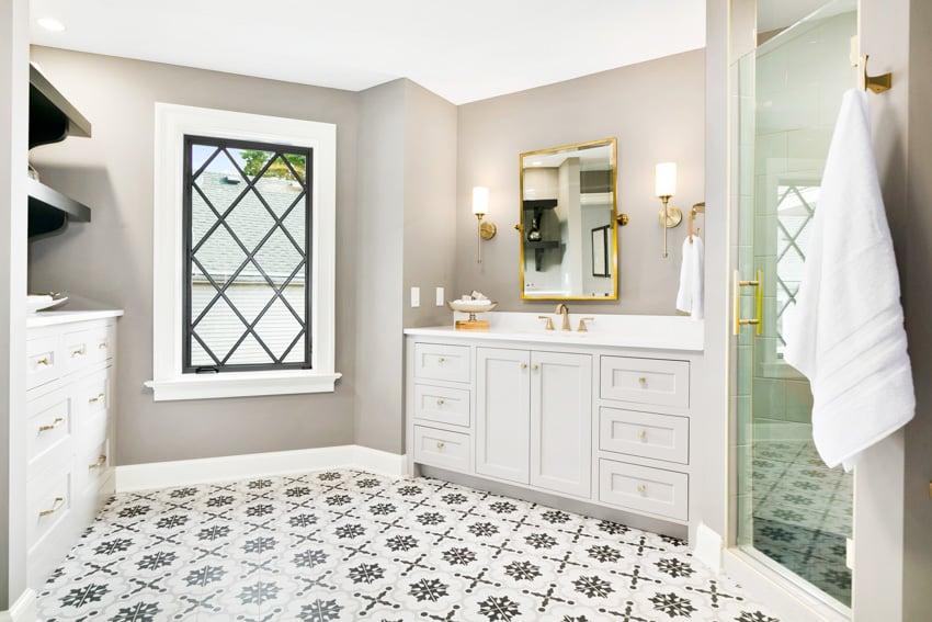 Bathroom with gray walls drawers patterned tile floor glass door window
