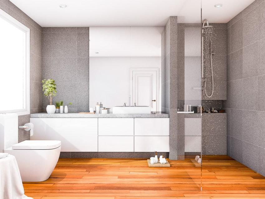 Bathroom with gray walls wood floor white cabinets mirror toilet