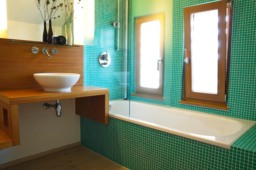 Bathroom with small green tiles frosted window wooden countertop basin sink bathtub