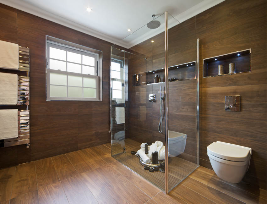 Bathroom with wood flooring walls glass shower area toilet obscure window
