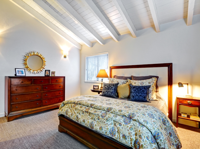 A beautiful classic master bedroom with vaulted white wood ceiling and cherry wood furniture