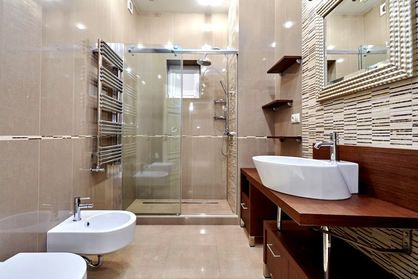 Beautiful fully tiled bathroom interior with wooden shelves and cabinets