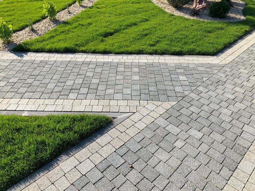 Beautiful garden nested with cobblestone pavers surrounded with green grass