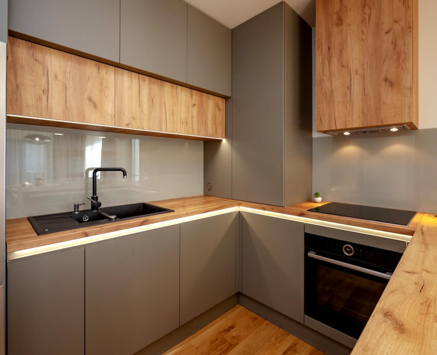 A beautiful grey modern kitchen in a luxury apartment with stainless steel appliances