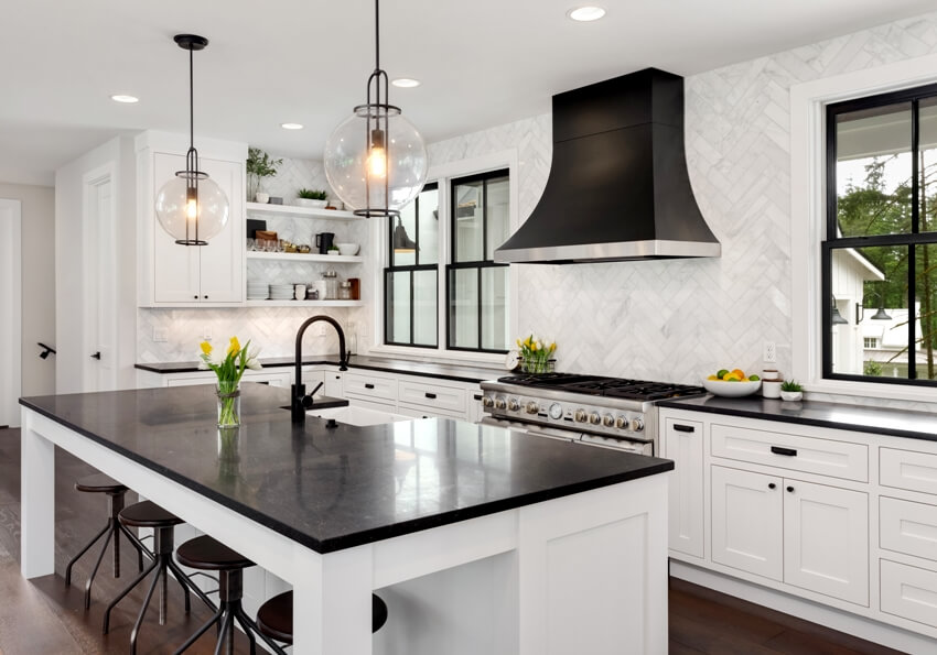 Beautiful kitchen features black counters full height backsplash and island with white woodwork and cabinetry
