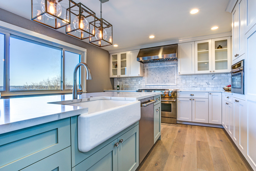 Beautiful kitchen interior with fireclay sink light fixtures and white cabinets