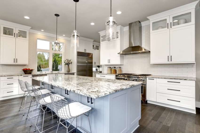 A beautiful kitchen with double stacked cabinets island and stainless steel chairs