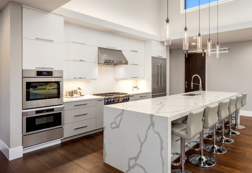 A beautiful modern kitchen with large waterfall island double ovens and hardwood floors