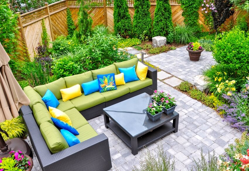 A beautiful small urban backyard garden featuring a tumbled paver patio with a variety of trees and shrubs