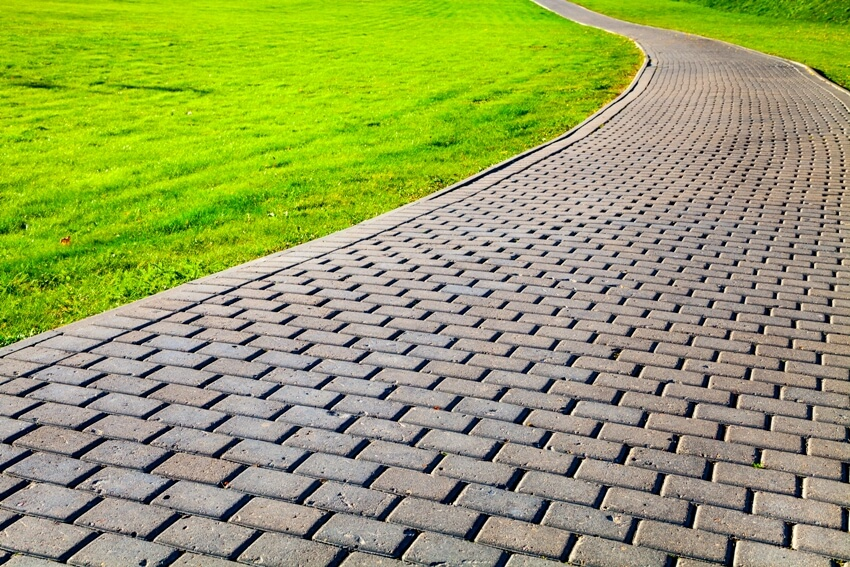 Beautiful summer city park walkway with cobblestone path and green lawn
