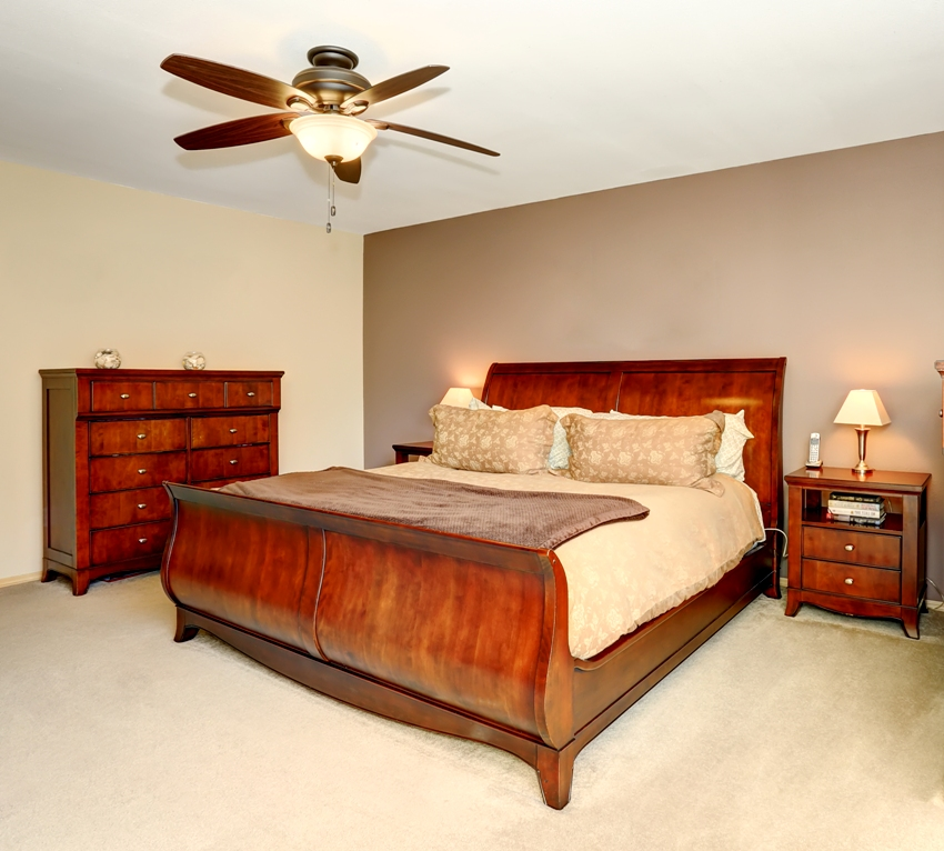 Bedroom interior with cherry wooden furniture and carpet floor