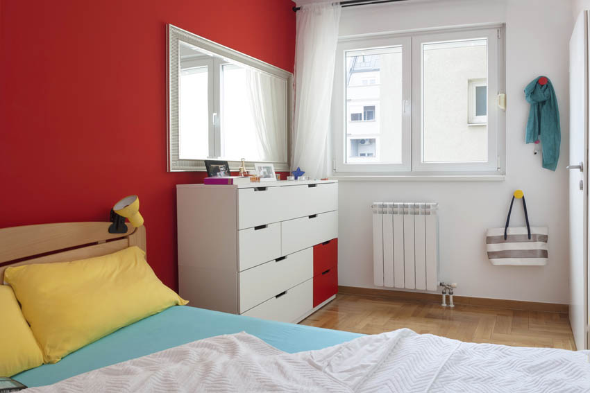 Bedroom interior with contrasting walls stylish dresser and mirror