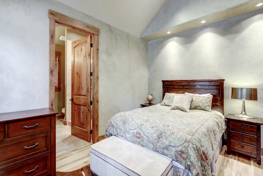 Bedroom interior with grey plaster venetian wall finish and cherry wood furniture