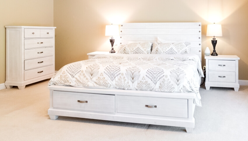 A bedroom with king sized bed with dresser and tribal print coverlet and pillows with warm gold colored walls and distressed white farm house style furniture