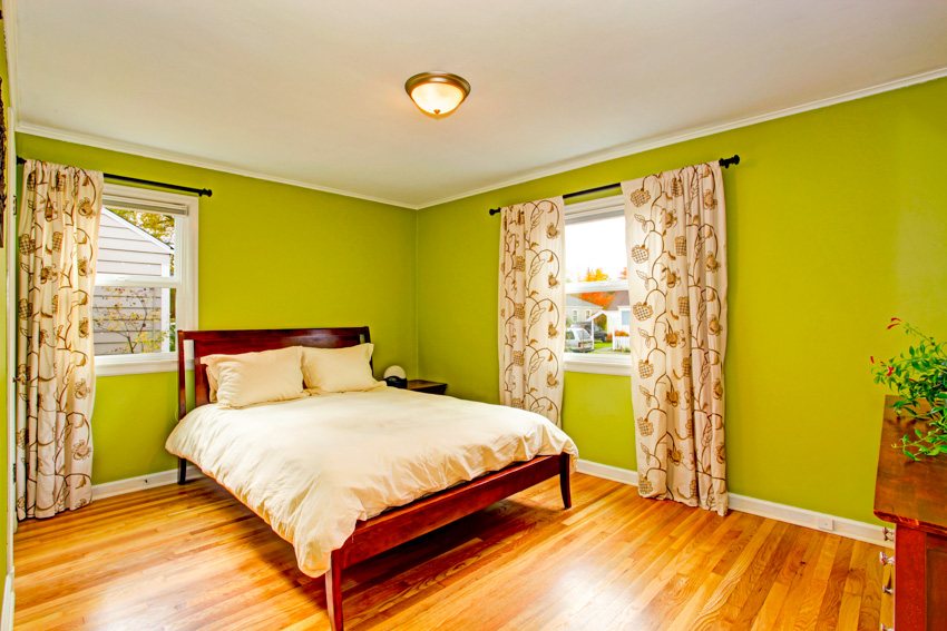 Bedroom with lime green wall curtain wood flooring