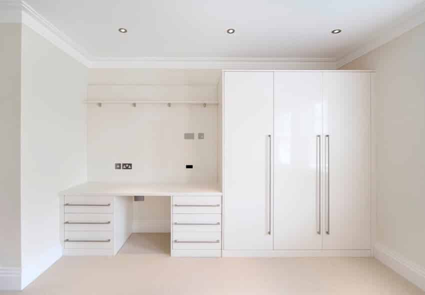 A bedroom with white walk in closet and a desk