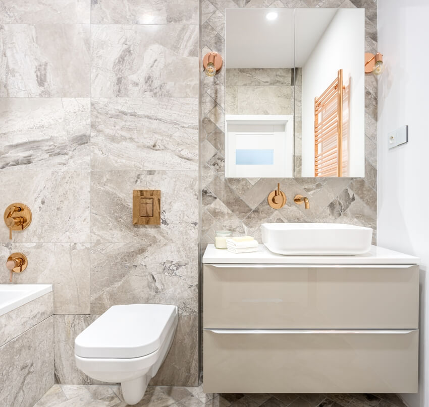 Beige bathroom with marble style tiles and copper details like taps lamps and wall heater