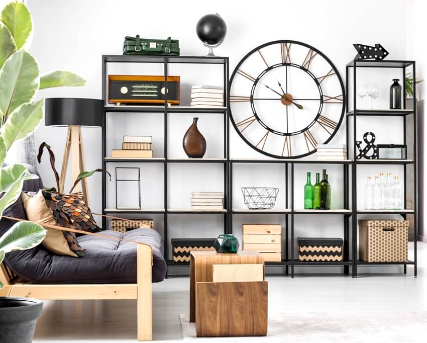 A big clock on industrial type bookcase with decorations in bright flat interior with black couch and wooden stool