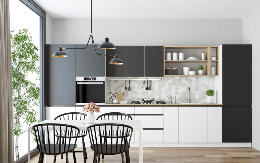 Black and white kitchen with hanging lights and large glass window wood floor
