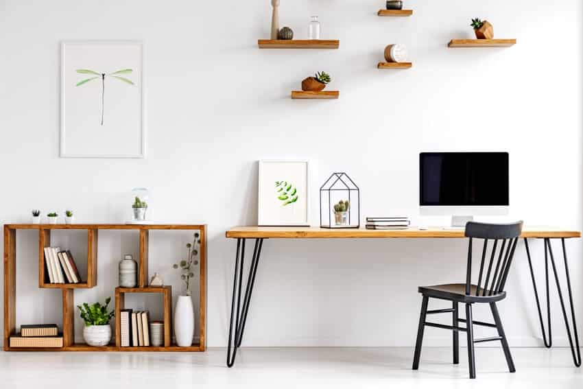 A black chair at table with computer monitor in bright home office interior with poster and rustic style bookcase