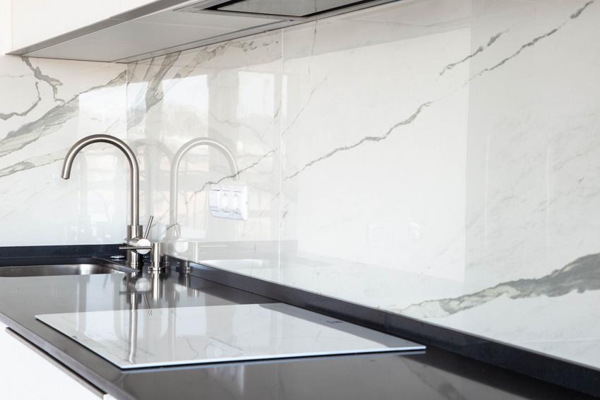 Black countertop with sink faucet marble backsplash