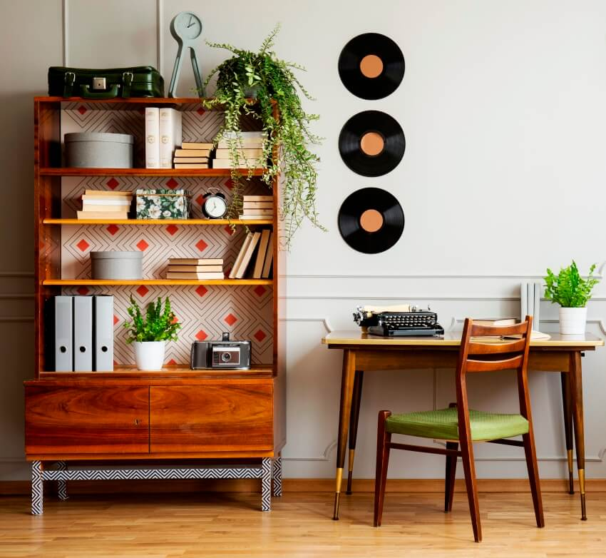 A black retro typewriter on a unique wooden desk a mid century modern chair and a renovated bookcase