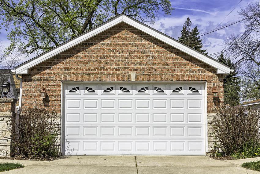 brick garage with vinyl door with decorative windows