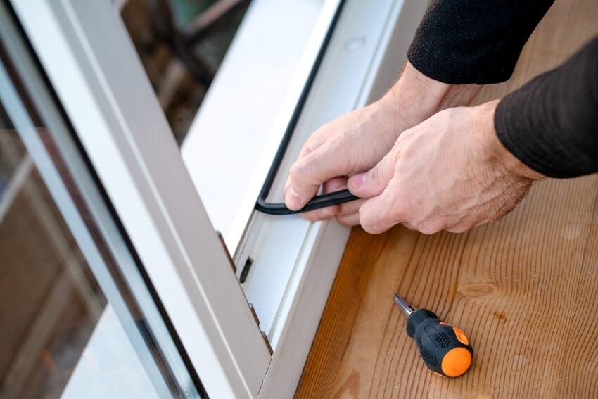 Man changing rubber tubular sweep seal gasket in pvc door