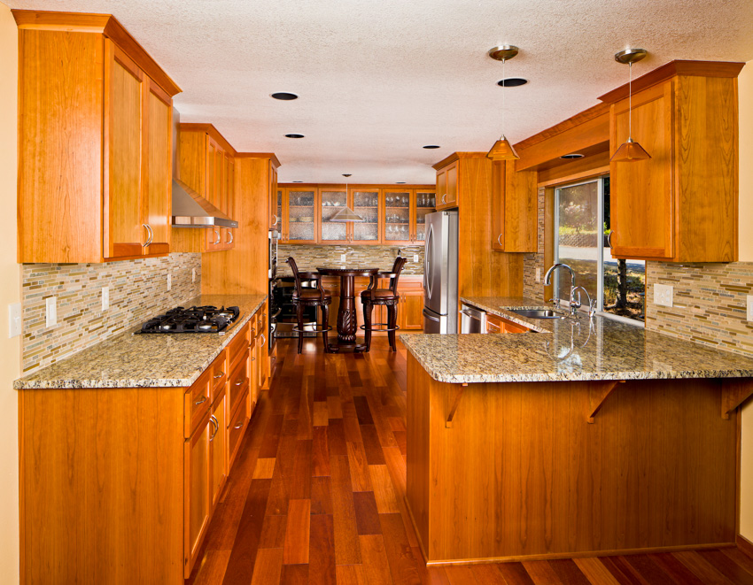 Cherry wood flooring cabinets drawers marble countertop stove