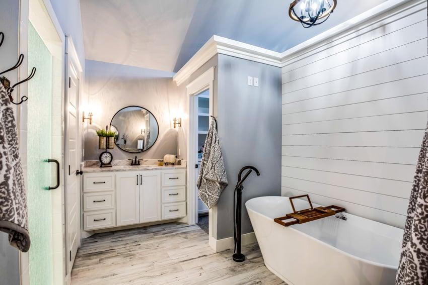 Classic bathroom tile floors white walls gray elements cabinets mirror bathttub