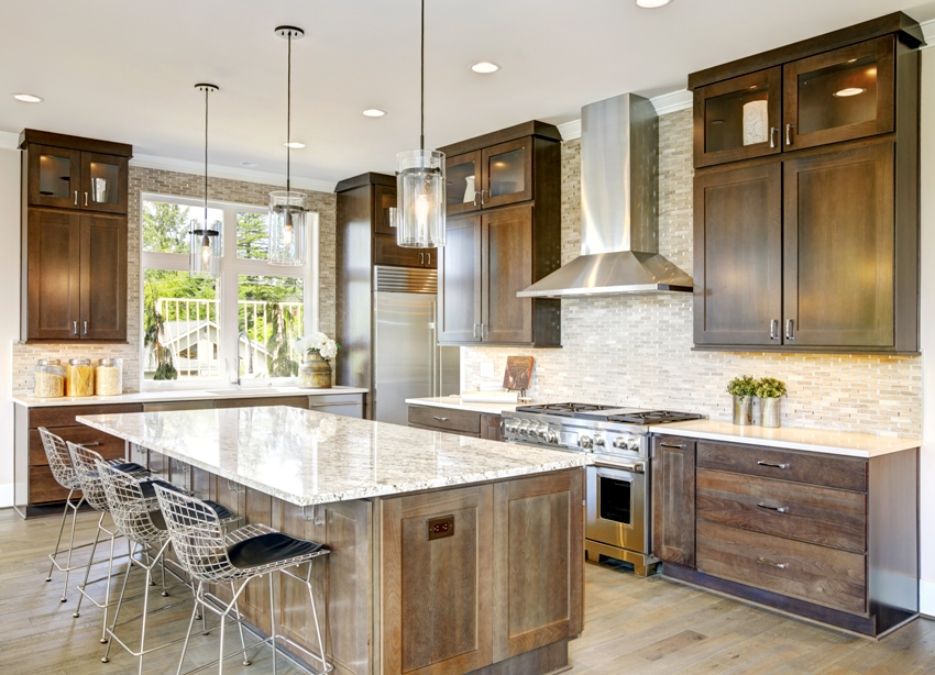 A classic kitchen interior with wooden cabinets island with chairs and marble countertop