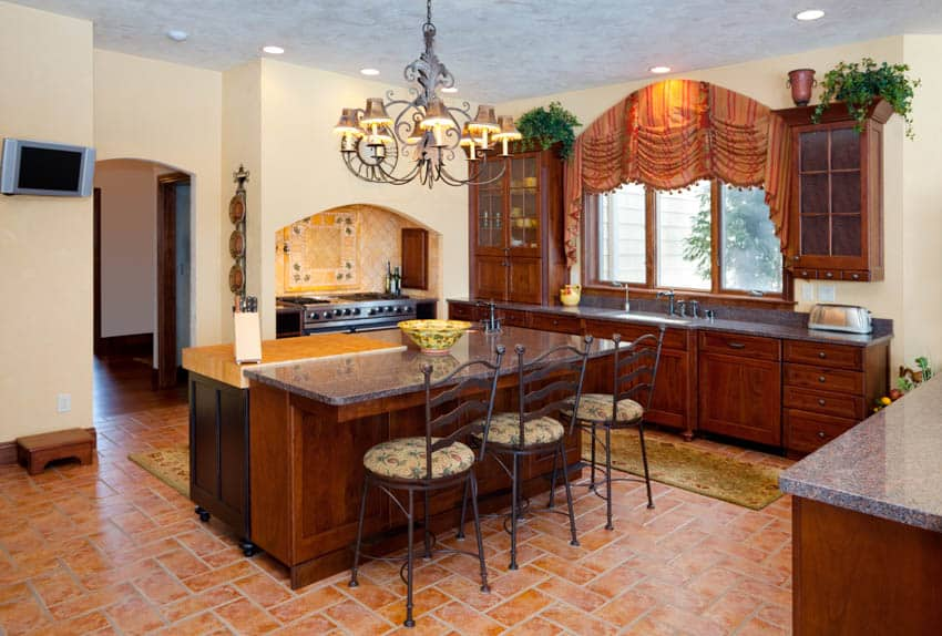 Classic kitchen space with center island for dining tile floor chandelier window maple cabinets