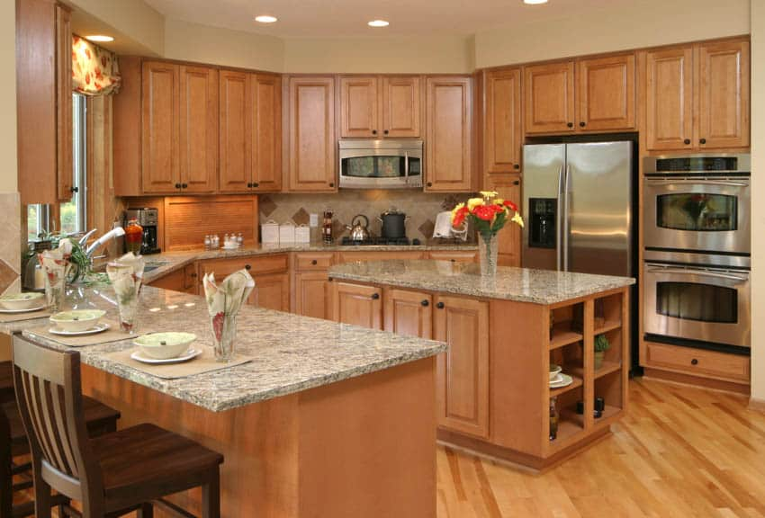 Classic kitchen space with light maple cabinets wood flooring center island dining area