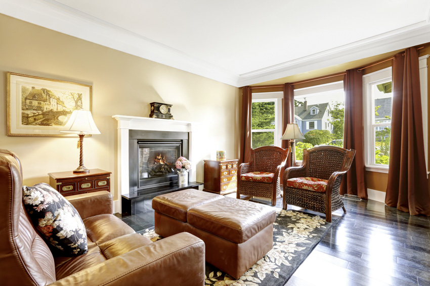 Classic living room with yellow walls rust colored curtains sofa leather chairs