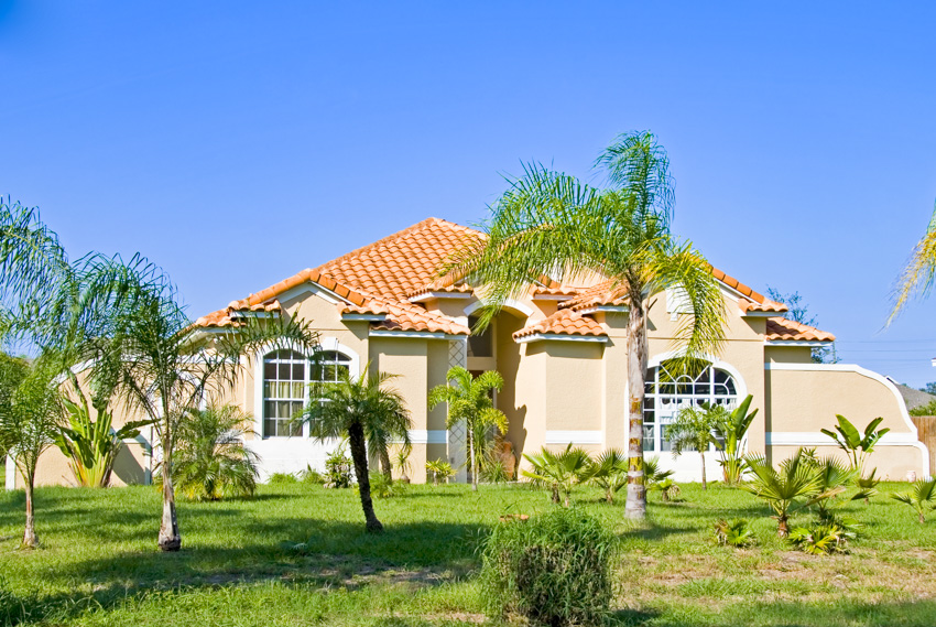 Classic spanish style house landscaped lawn palm trees